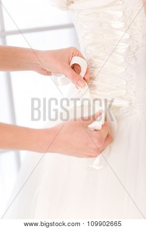Closeup portrait of a bride putting white wedding dress