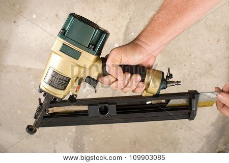 Carpenter loading more nails into an angle nail gun with the warning label that all power tools have on them shown illustrating safety concept