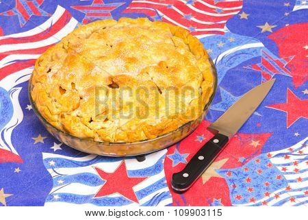 Apple pie on an American flag background, symbols of Americana