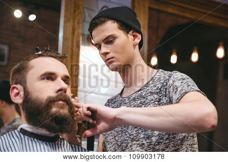 Young skillful barber making haircut to handsome bearded man in barbershop