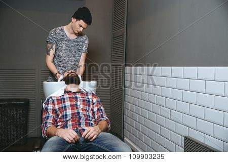 Young handsome barber with tatoo in black hat washing hair of client with beard in plaid shirt and jeans in barbershop