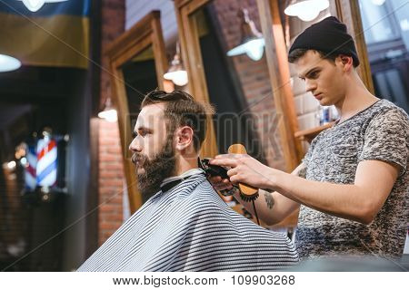 Barber making haircut to handsome attractive man with beard and working with electric razor