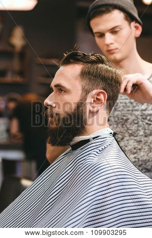 Professional hairdresser cutting young bearded man's hair in hairdressing salon