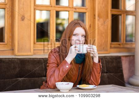 Pensive woman with beautiful long red hair sitting with coffee cup  and dreaming in outdoor cafe