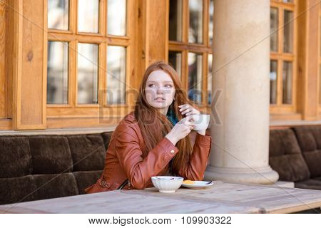 Young beautiful pencive redhead lady in leather jacket drinking coffee in a street cafe