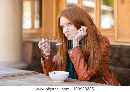 Cute content young woman with beautiful long red hair having breakfast in outdoor cafe and talking on cellphone biting bottom lip