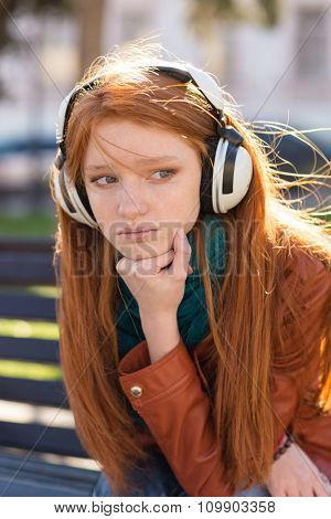 Portrait of beautiful sad pensive young woman with long red hair in headphones sitting in the park