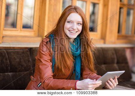 Happy joyful redhead young woman in leather jacket and scarf using tablet and smiling in open air cafe