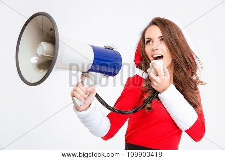 Portrait of beautiful joyful young lady in red santa claus costume with hood using loudspeaker isolated over white background