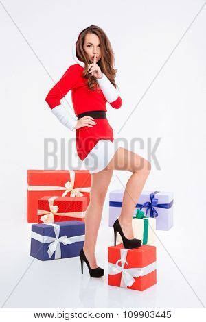 Full length portrait of a young woman in santa claus cloth standing near gift boxes and showing finger over lips isolated on a white background