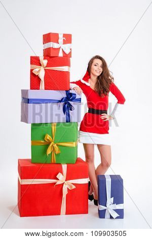 Full length portrait of cheerful beautiful young woman in red santa claus dress with colorful christmas presents isolated over white background