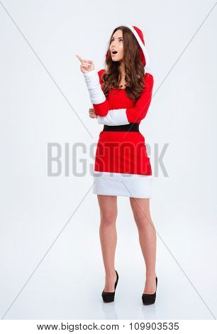 Surprised excited attractive curly girl in santa claus dress with hood pointing up and looking up standing over white background