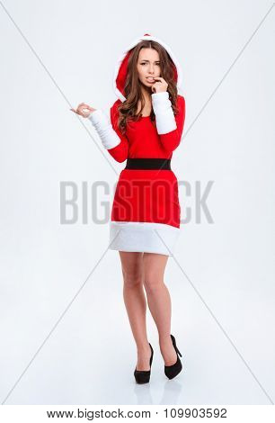 Unconfident embarrassed young curly female in red santa claus costume with hood pointing away over white background