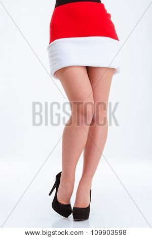 Closeup portrait of a sexy female legs in santa claus cloth and high heels isolated on a white bakground