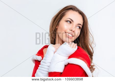 Pleased happy lovely young female in red santa claus costume over white background