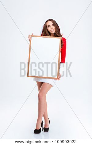 Full length portrait of pretty happy content young lady in santa's clothes with hood posing with blank board over white background