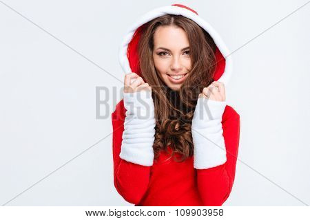 Beautiful cheerful curly young woman in red santa claus costume with hood isolated over white background