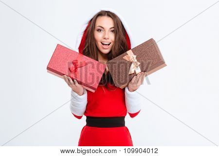 Amazed lovely excited girl in red santa claus costume with hood holding two presents isolated over white background