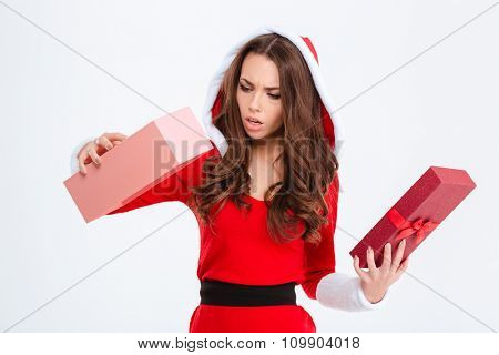 Disappointed shocked curly young woman in red santa claus costume with hood got empty gift over white background