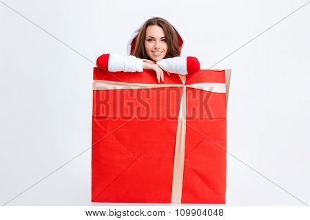 Pretty joyful smiling young woman in red santa claus costume with hood sitting inside the present box over white background