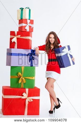 Full length portrait of beautiful happy young woman in red santa claus dress with hood posing with colorful present boxes over white background