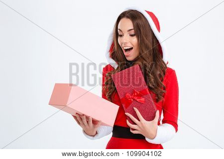 Surprised happy content curly young female in red santa claus costume with hood looking inside present box on white background