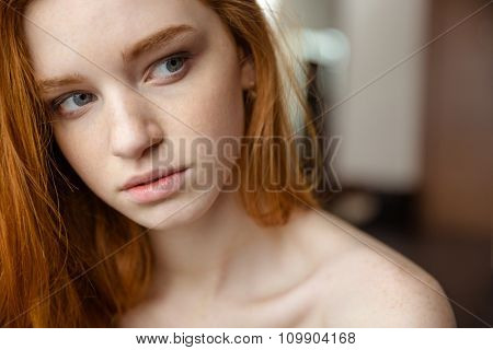 Beauty portrait of sensual thoughtful young woman with red hair looking away