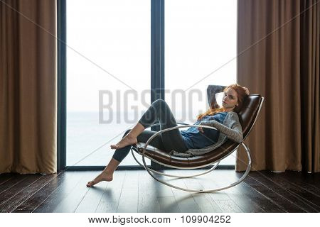 Portrait of a beautiful redhead woman sitting on rocking chair at home