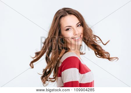 Portrait of a smiling pretty woman turning around and looking at camera isolated on a white background