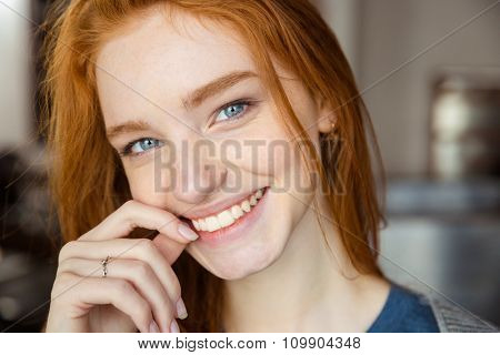 Closeup portrait of a smiling redhead woman looking at camera