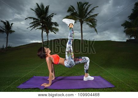 Side view of young woman doing gymnastics the bridge pose