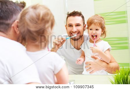 Happy Family Father And Child Girl Brushing Her Teeth In Bathroom Toothbrushes