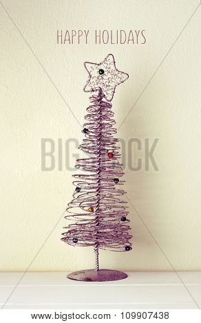 a simplified christmas tree made of wire against a white wall and the text happy holidays, with a filter effect