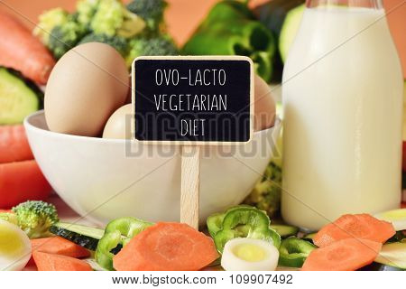 closeup of a signboard with the text ovo-lacto vegetarian diet on a table full of different raw vegetables, a bowl with some chicken eggs and a bottle with milk