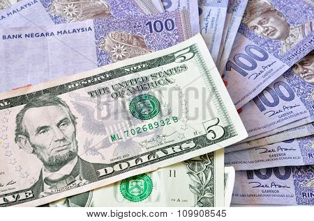 A Close-up Photograph Of United States Dollars And Ringgit Malaysia Currency.