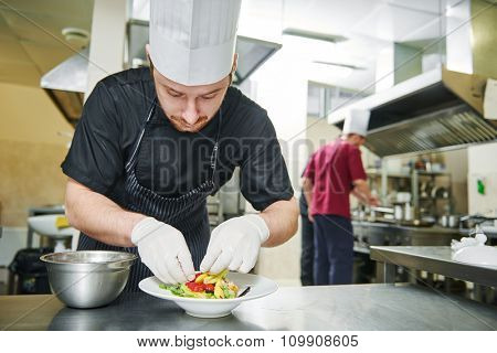 male cook chef decorating garnishing prepared salad dish on the plate in restaurant commercial kitchen