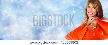 Shopping woman with  gifts over blue background.