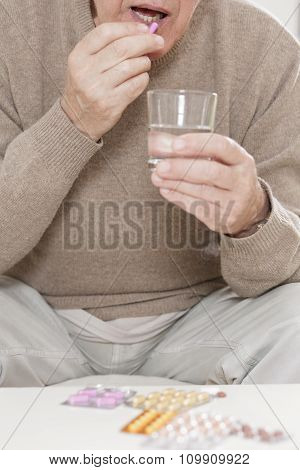 Old Man Taking Tablet