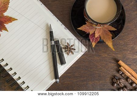 Coffee Beans, Cup Of Coffee, Autumn Leaves, Pen And Notebook On Wooden Deck