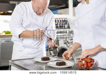 Chef decorates dessert cake with chocolate sauce in kitchen
