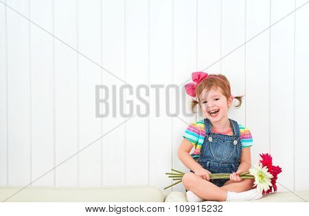 Happy  Child Little Girl With Bouquet Of Gerbera Flowers In Empty White Wall