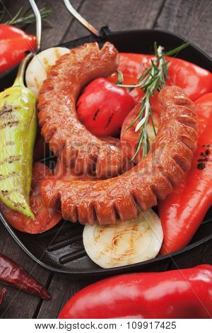 Grilled german sausages and vegetable in grilling pan