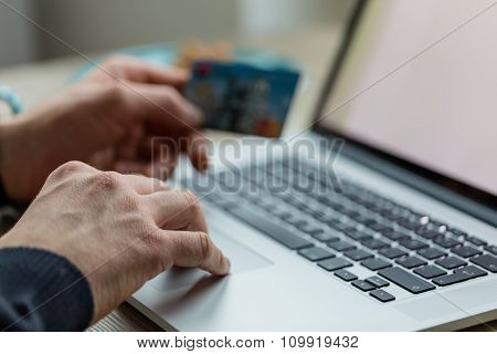Man working on notebook with credit card.