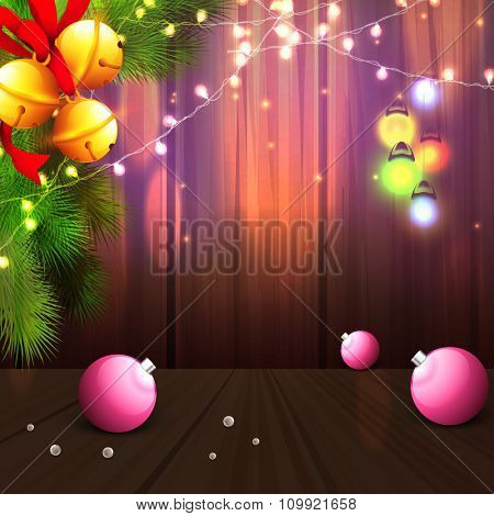 Merry Christmas celebration with glossy Xmas Balls, golden Jingle Bells, Fir Tree branch and illuminated lights on elegant wooden background.