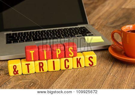 Tips & Tricks written on a wooden cube in a office desk