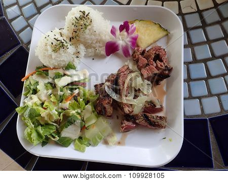 Slices Of Meat Steak, White Rice, Pineapple Slice, Flower, And Salad With Dressing