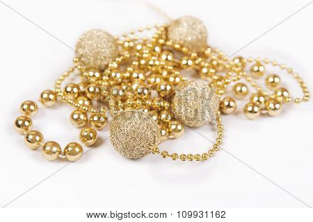 Gold Gift With Other Christmas Baubles Like Holiday Decoration On White.