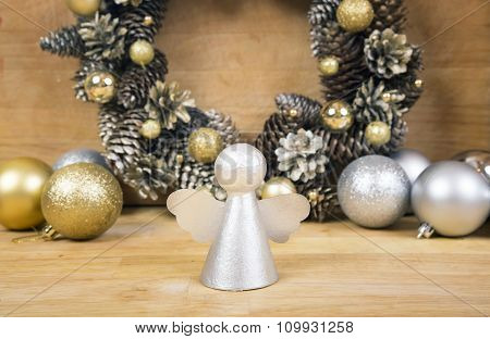 Christmas Angel With Wreath Of Cones On Background.