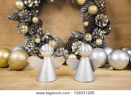 Christmas Angels With Wreath Of Cones On Background.