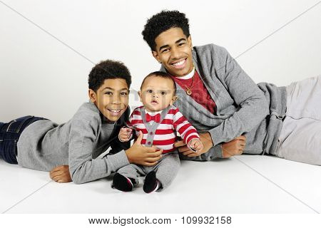 Portrait of three widely-spaced brothers:  a happy older teen and elementary boy with their baby brother.  On a gray background.